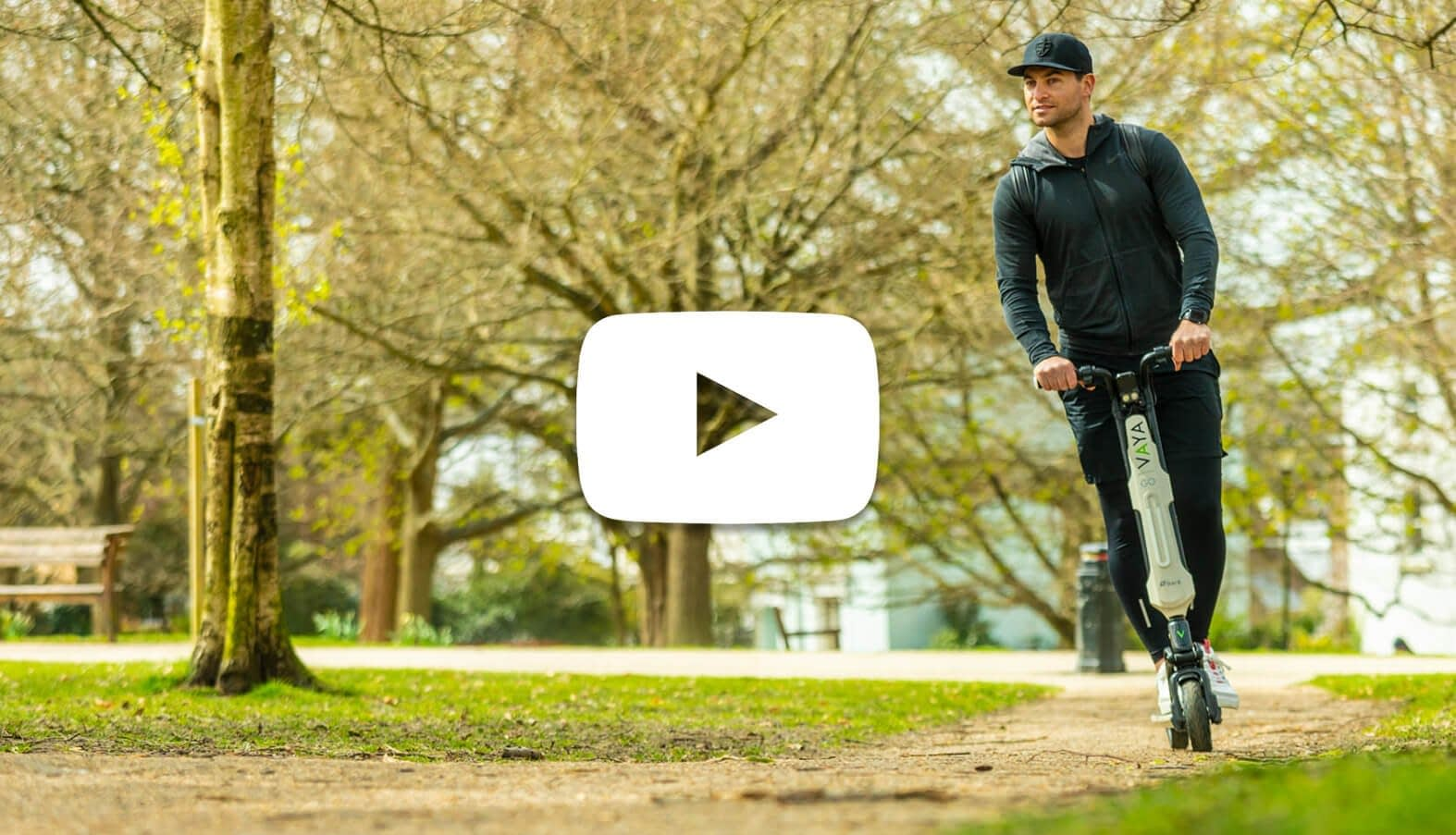 young man riding scooter through park in London